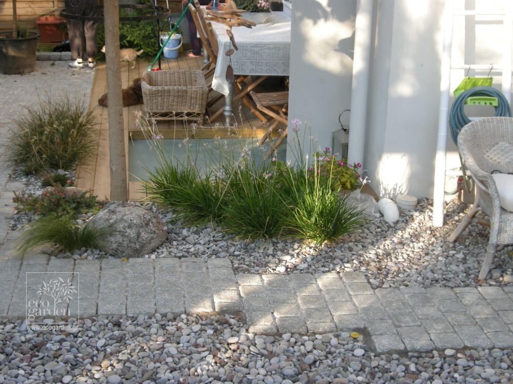 Μονοπάτι από κυβόλιθους μέσα στο βότσαλο δίνει κατεύθυνση μέσα στον κήπο.